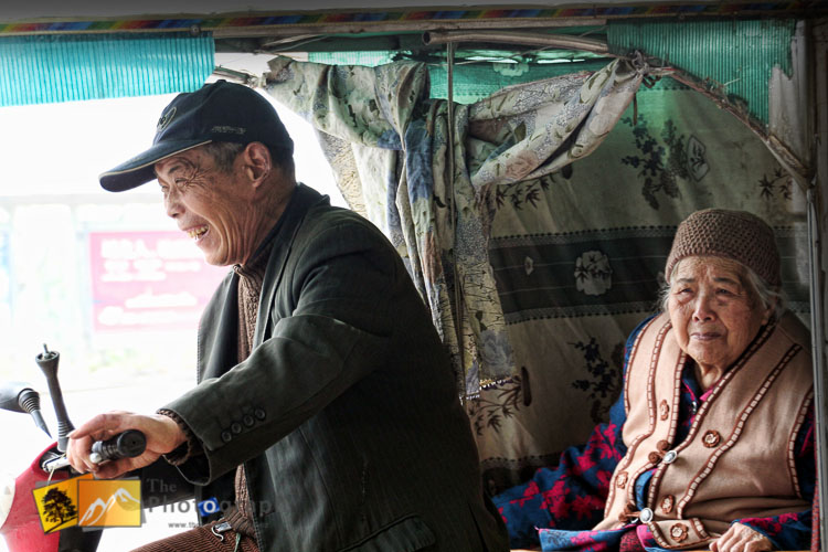 Old couple riding chinese rickshaw
